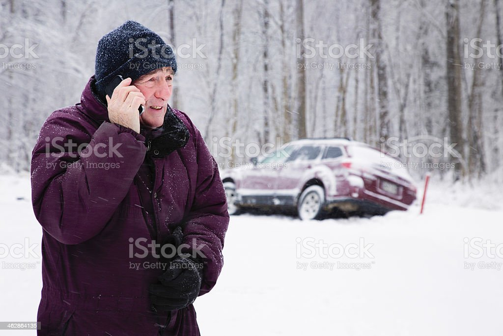 Senior man calling for help during snow storm stock photo