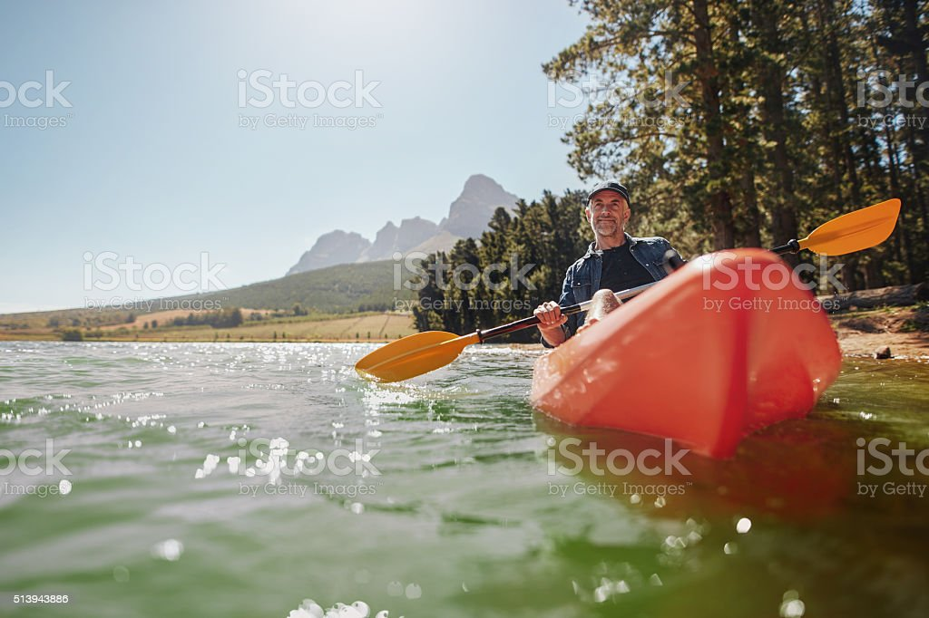 Senior man canoeing in a lake on a sunny day stock photo