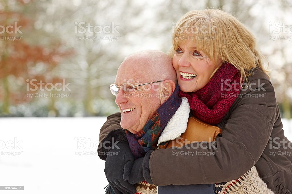 Senior man carrying his wife on back at winter park royalty-free stock photo