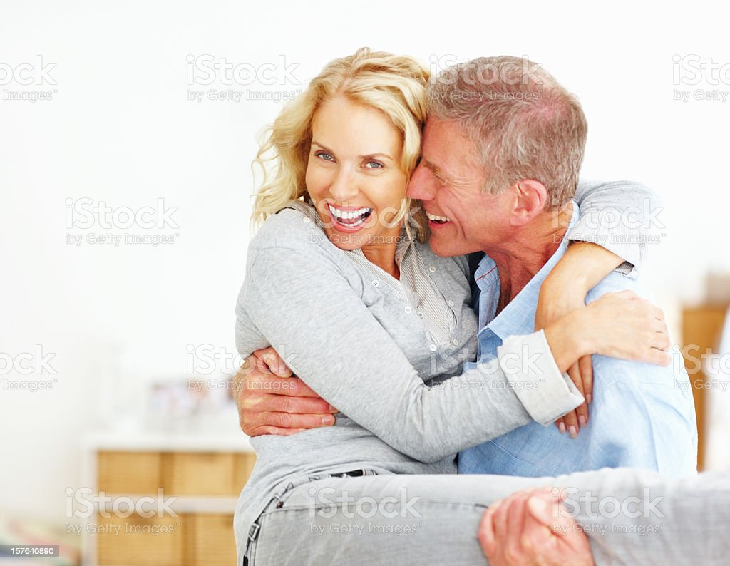 Senior man carrying mature woman in arms stock photo
