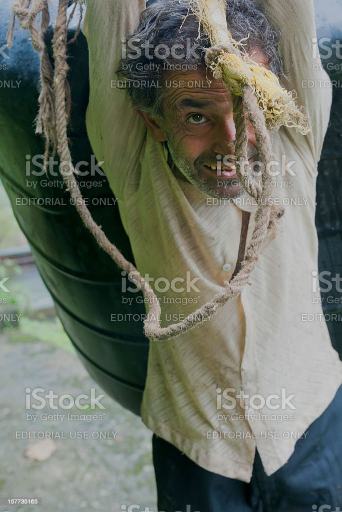 Senior Man Carrying Water Sikkim India stock photo