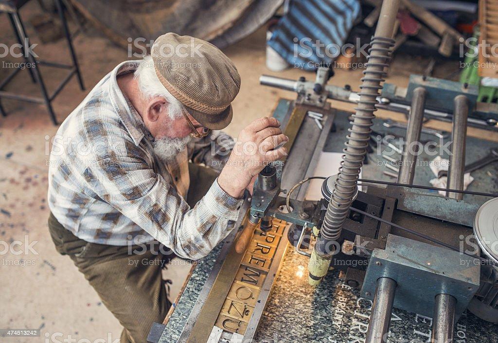 Senior man carving stock photo