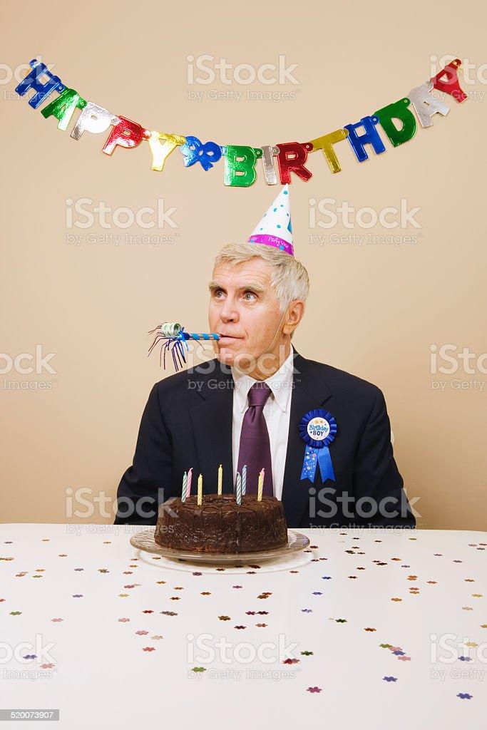 Senior man celebrating birthday, indoors stock photo