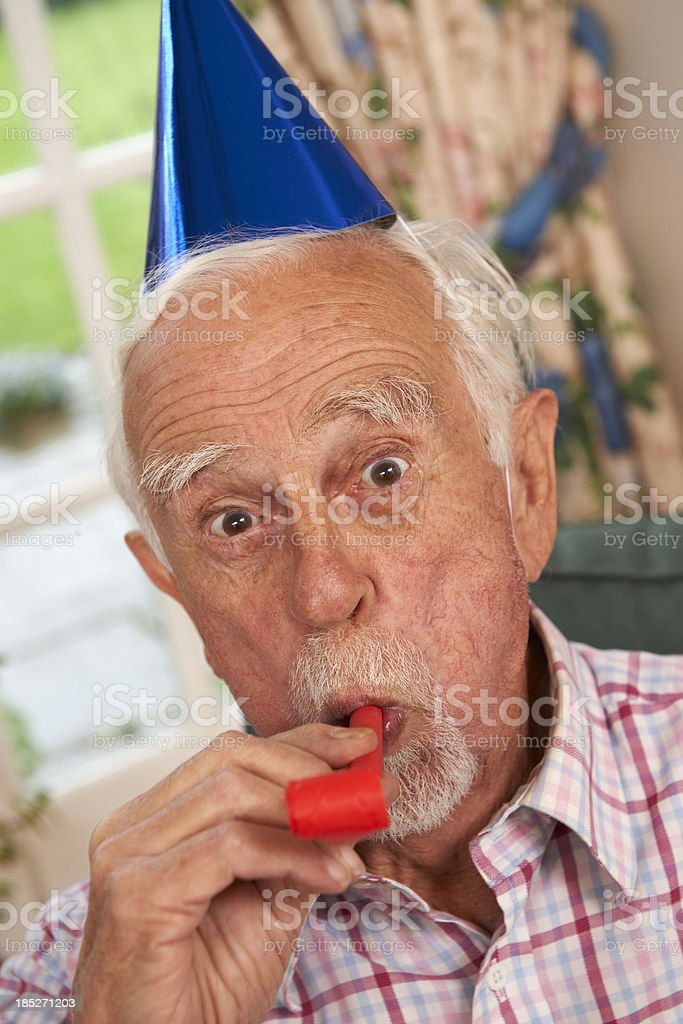 Senior Man Celebrating With Party Hat And Blower stock photo