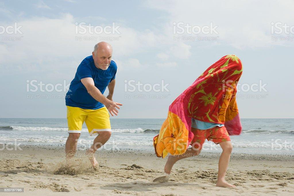 Senior man chasing boy running along beach stock photo