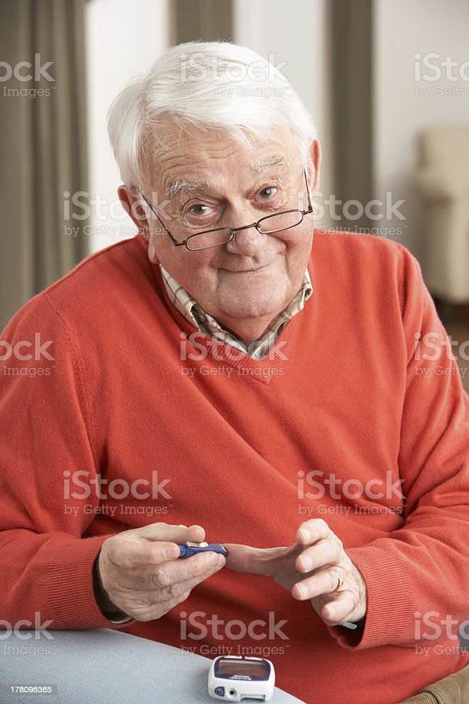 Senior Man Checking Blood Sugar Level At Home royalty-free stock photo