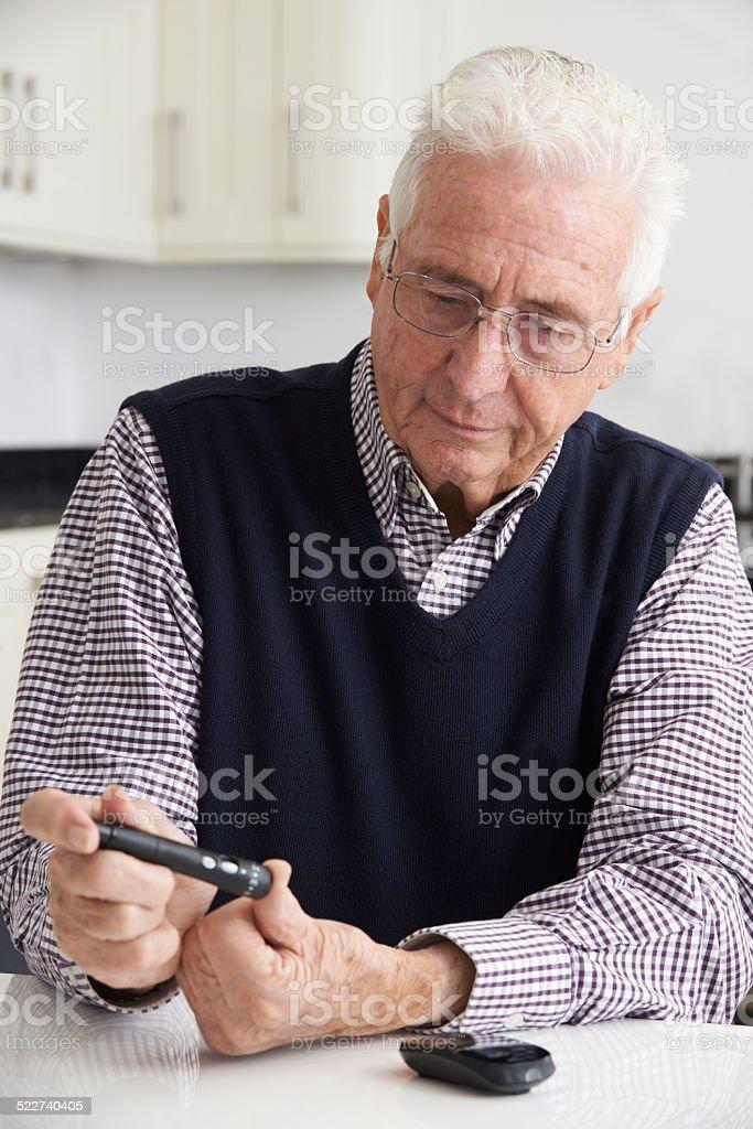 Senior Man Checking Blood Sugar Level At Home stock photo