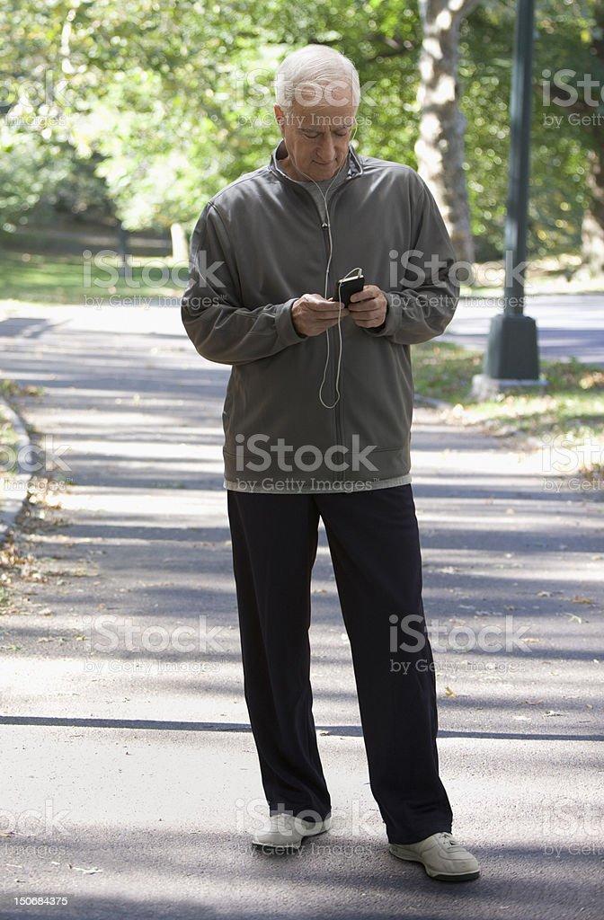 Senior man checking mp3 player outdoors royalty-free stock photo
