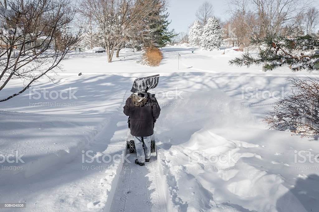 Senior Man Clearing Snow After a Blizzard stock photo