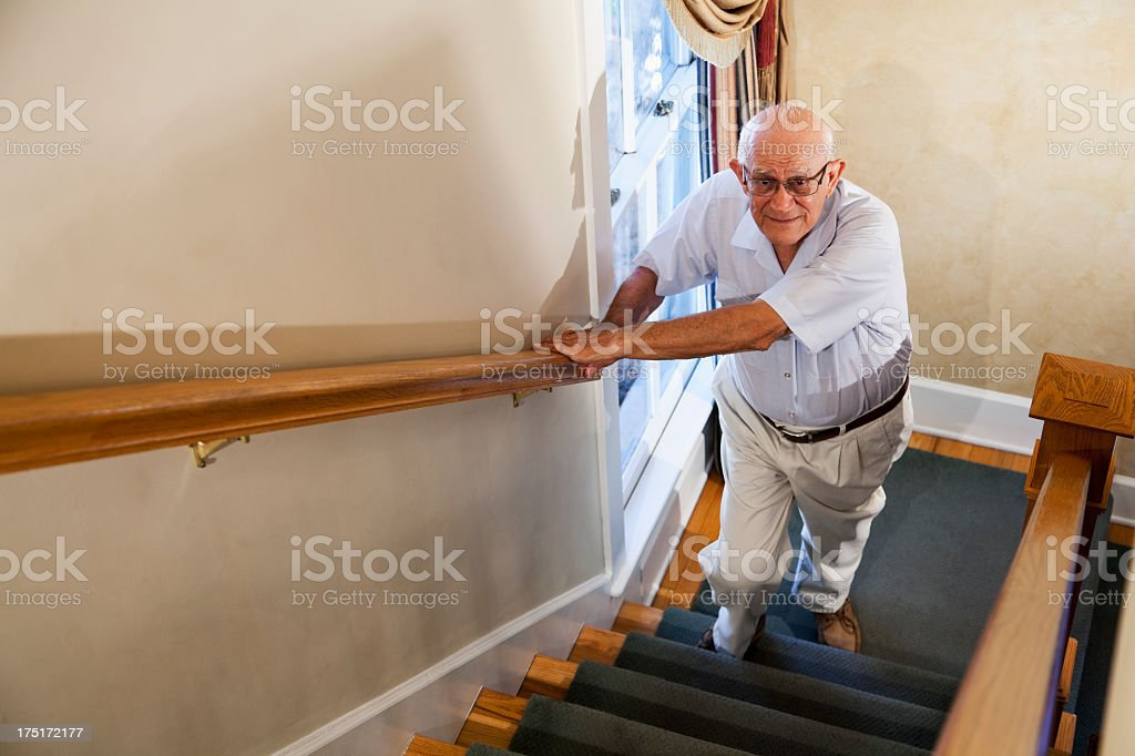 Senior man climbing stairs stock photo