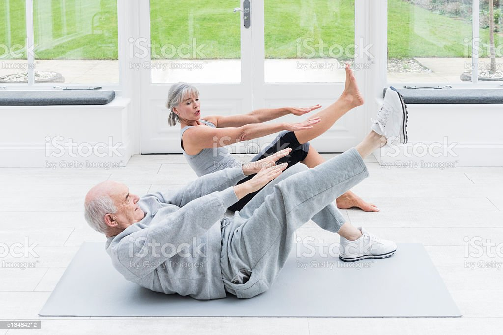 Senior man copying female fitenss instructor stretching legs stock photo