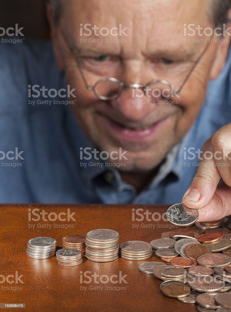 Senior man counting cash into piles royalty-free stock photo