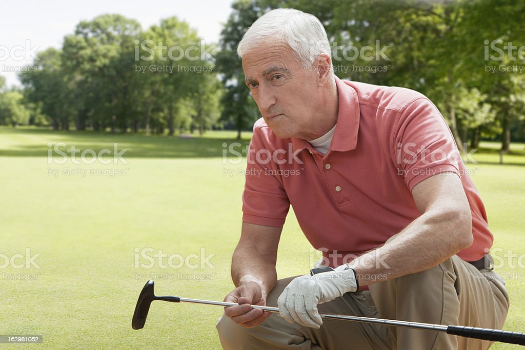 Senior man crouching with a golf club royalty-free stock photo