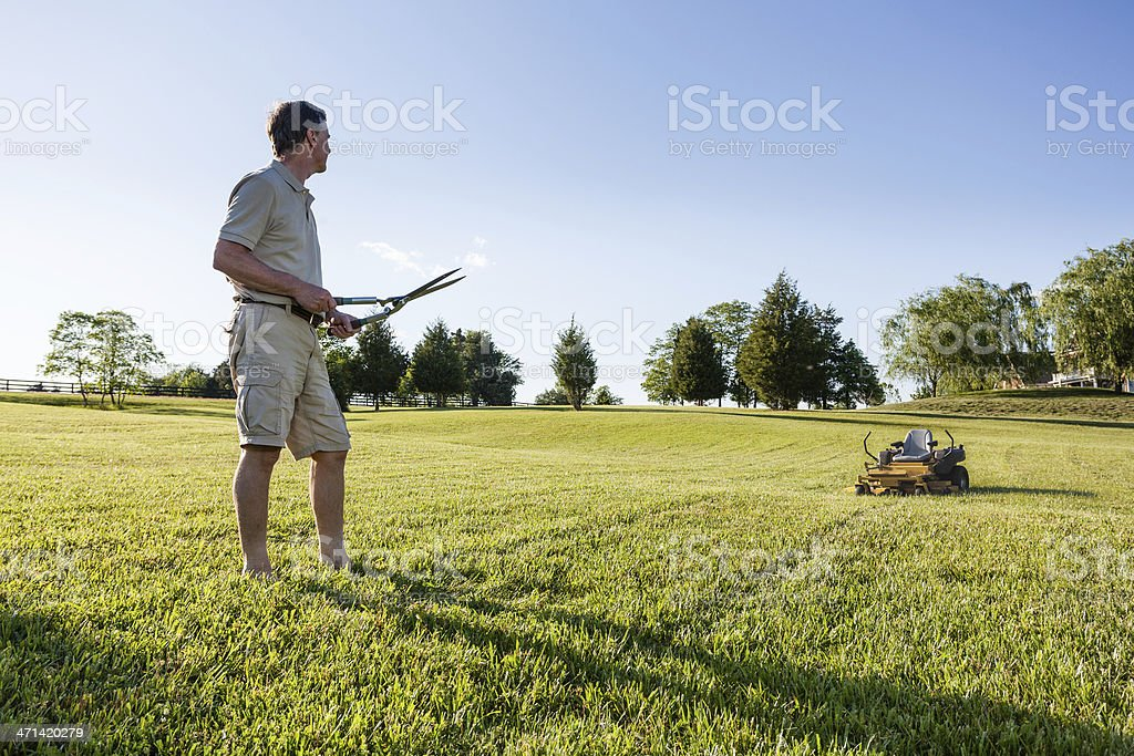 Senior man cutting grass with shears royalty-free stock photo