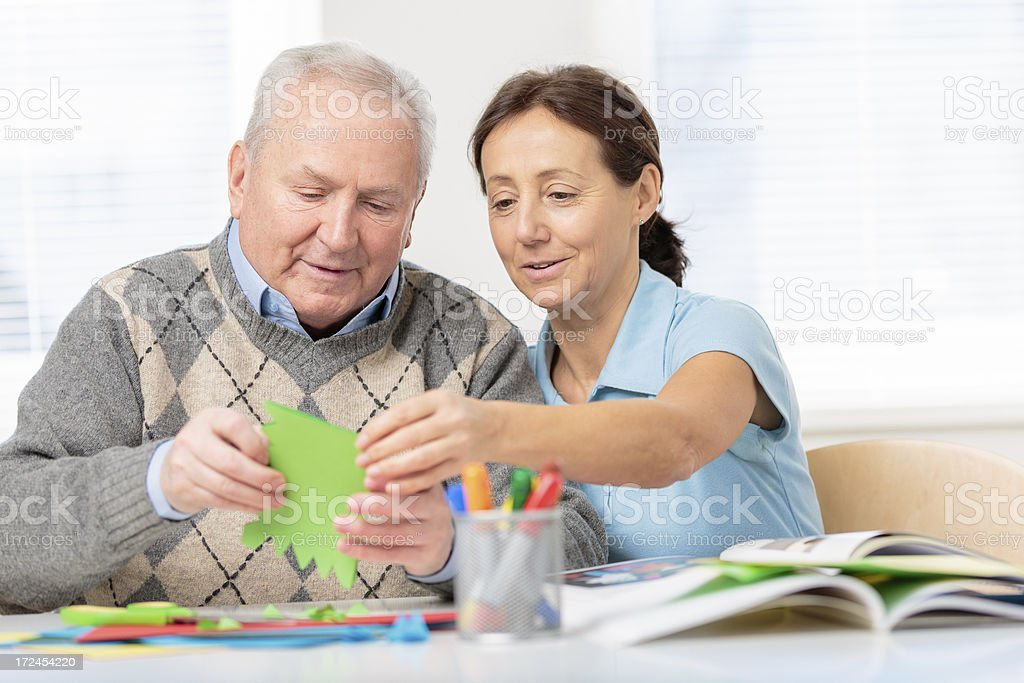 Senior man cutting paper with scissors stock photo