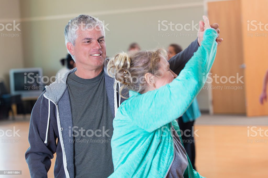 Senior man dances with wife at senior center stock photo