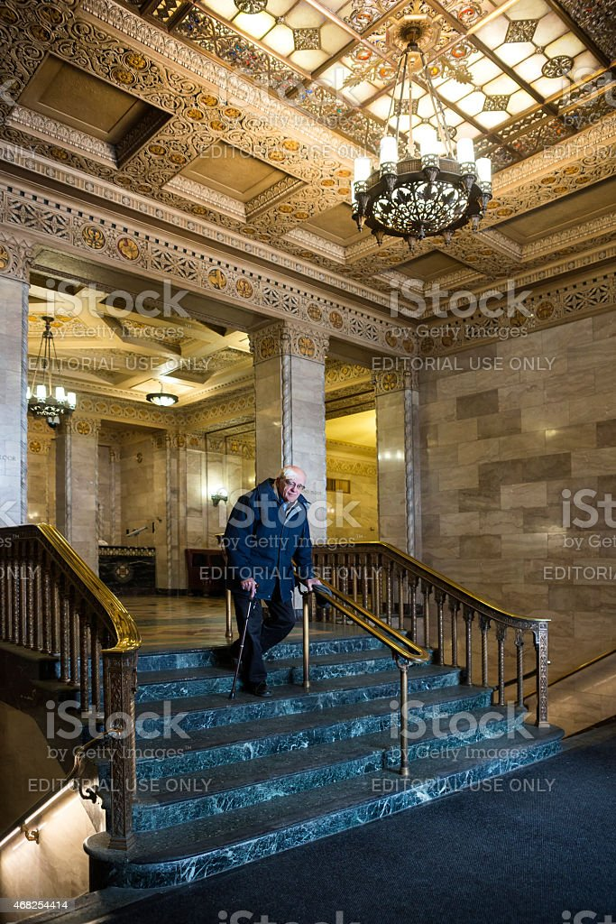 Senior man descends marble stairs with cane stock photo