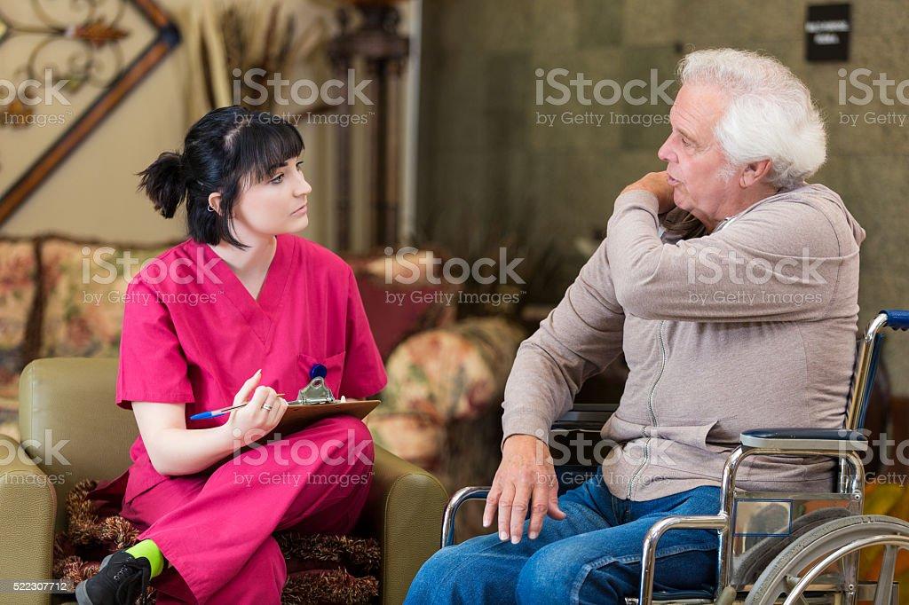 Senior man describes symptoms to nurse stock photo
