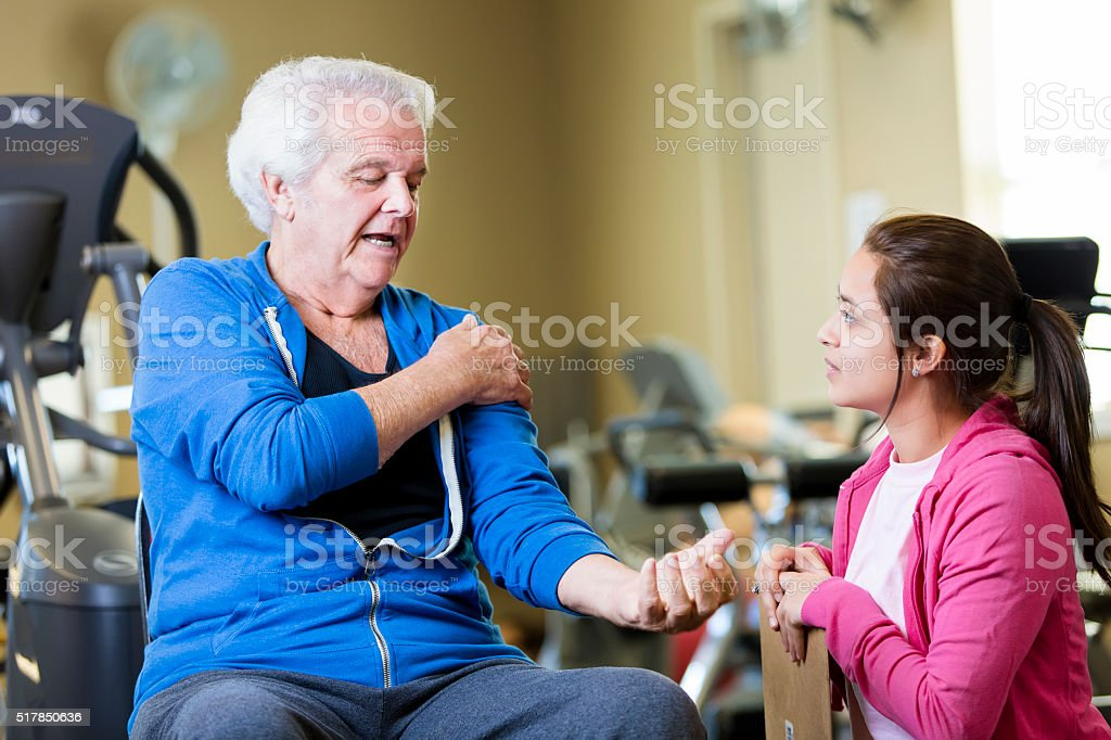 Senior man discusses pain with physical therapist stock photo