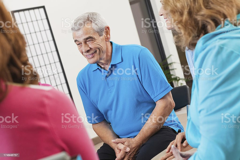 Senior man discussing things during support group or team meeting royalty-free stock photo