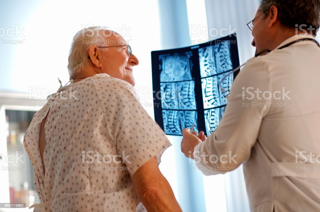Senior man discussing x-ray with doctor. stock photo