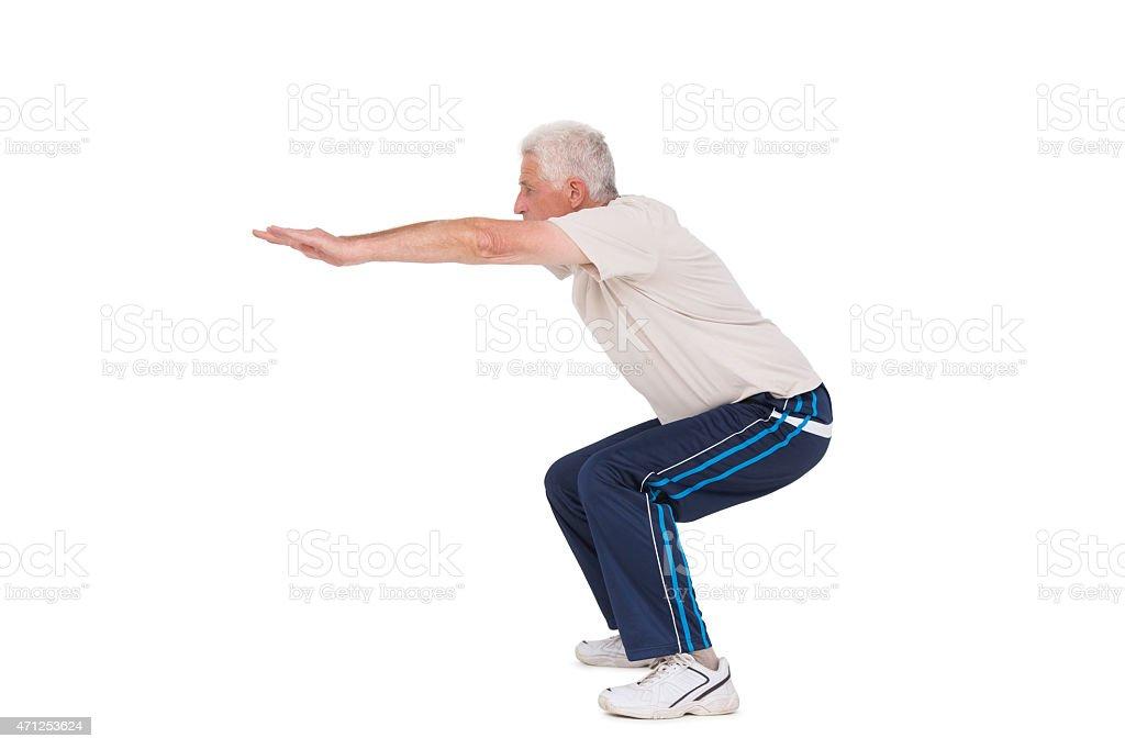 Senior man doing a squat stock photo