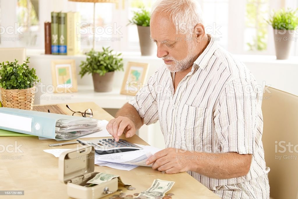 Senior man doing calculation at home royalty-free stock photo