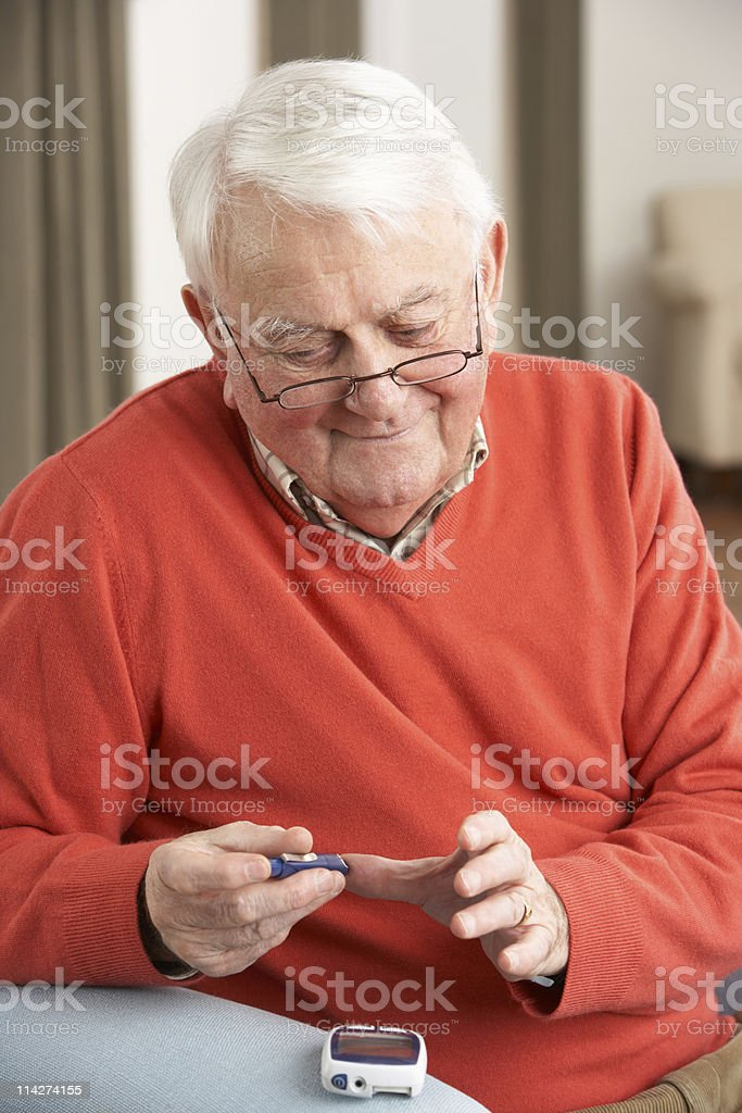 Senior man doing glucose blood test at his home stock photo
