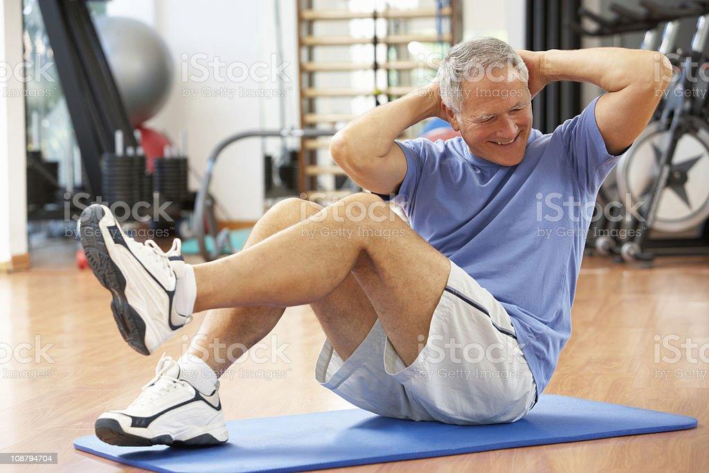 Senior Man Doing Sit Ups In Gym stock photo