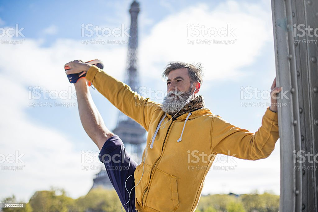Senior man doing stretching exercises in the street stock photo
