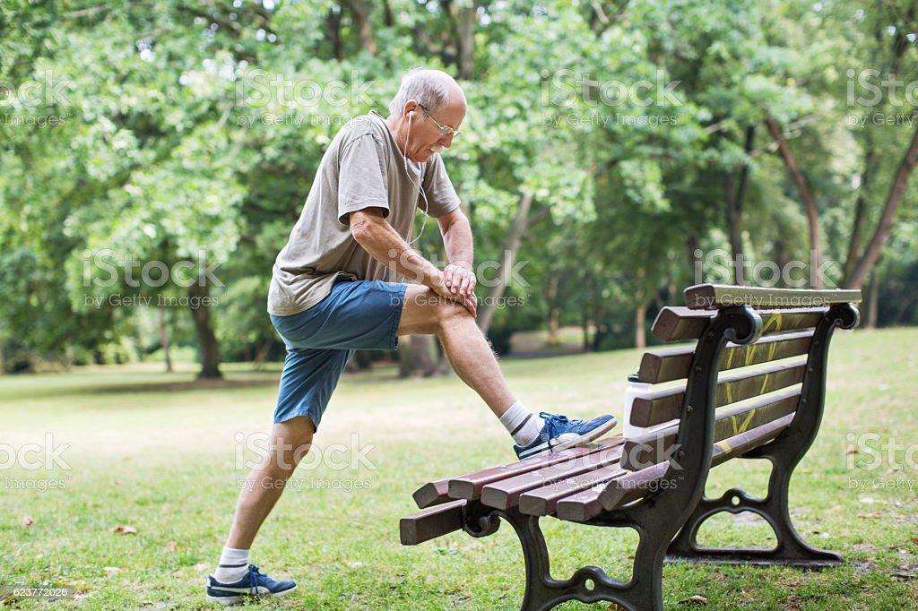 Senior man doing stretching in park stock photo