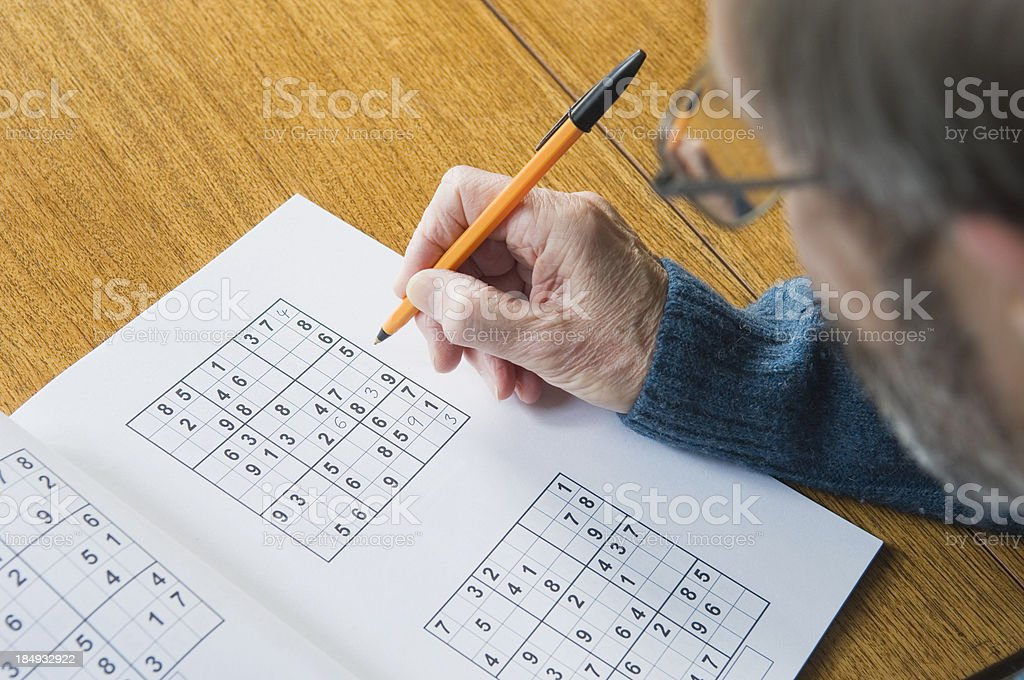 Senior man doing sudoku puzzle royalty-free stock photo