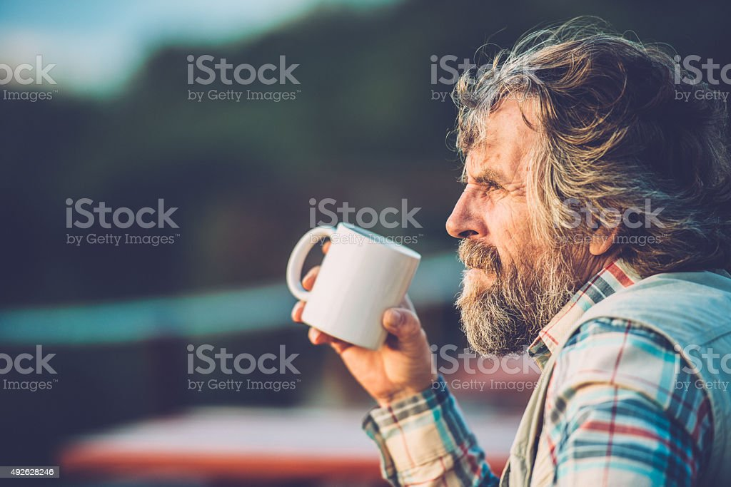 Senior Man Drinking a Coffee or a Tea Outdoors, Close-up stock photo