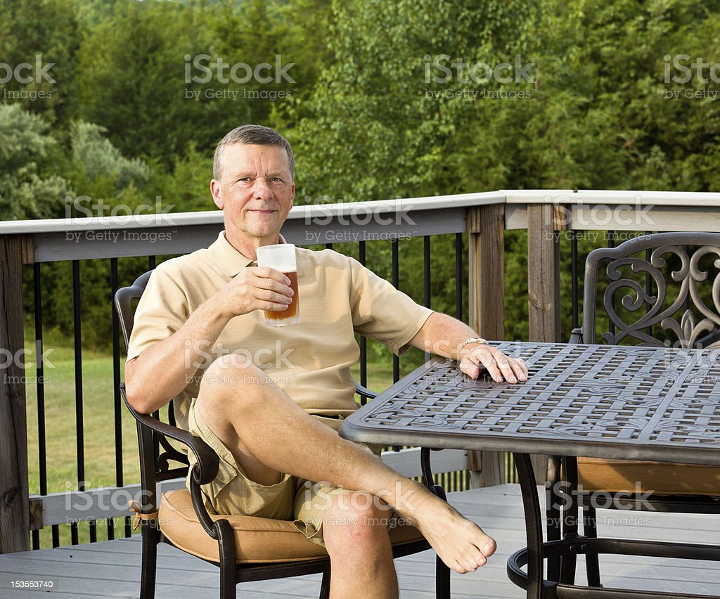 Senior man drinking beer in garden royalty-free stock photo