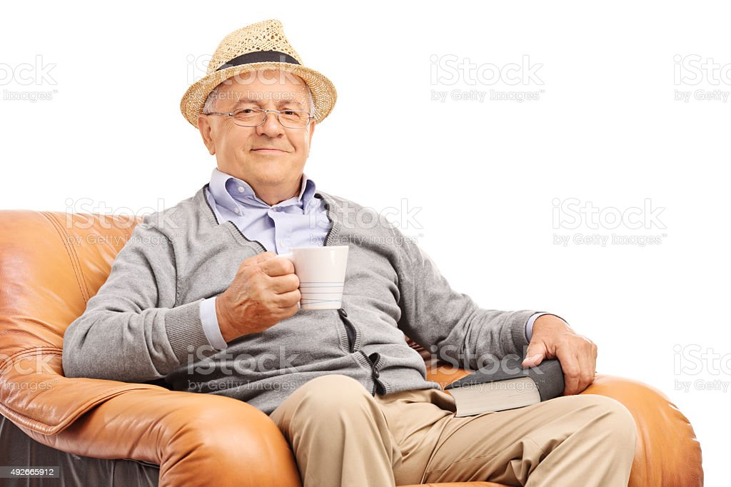 Senior man drinking coffee seated in an armchair stock photo