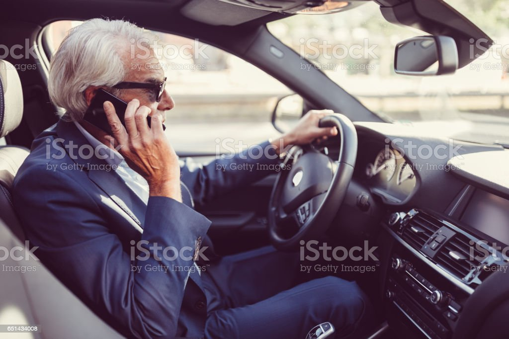 Senior man driving a car stock photo