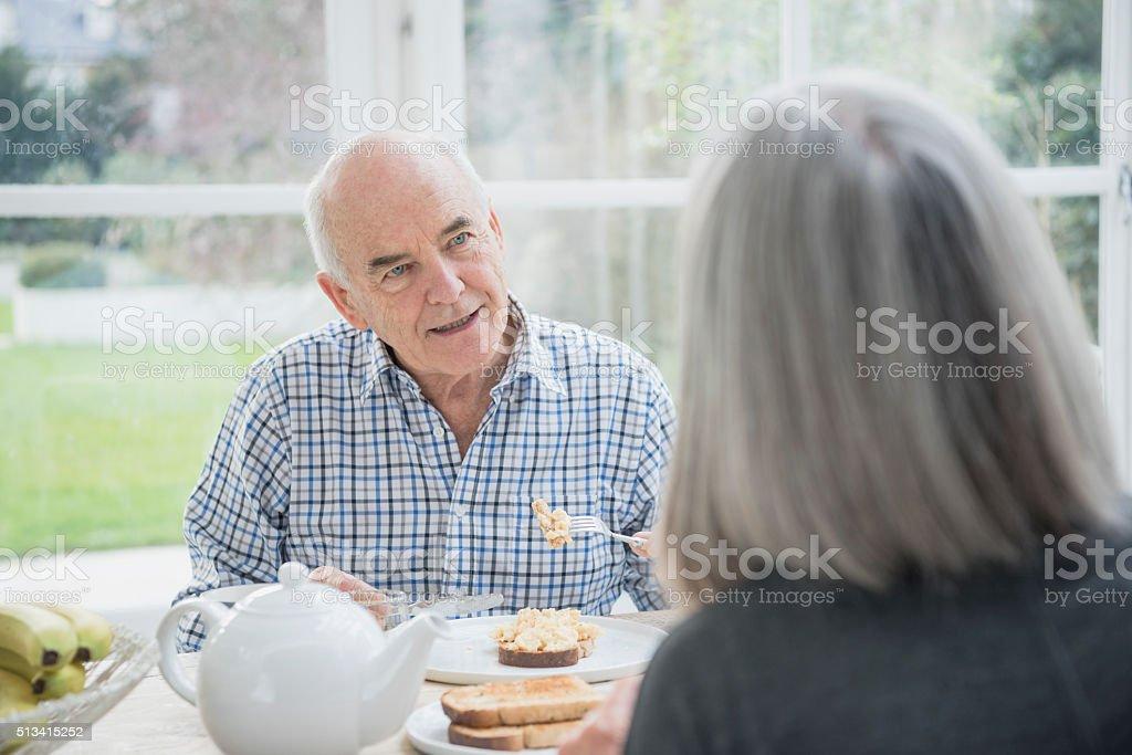 Senior man eating breakfast, listening to his wife stock photo