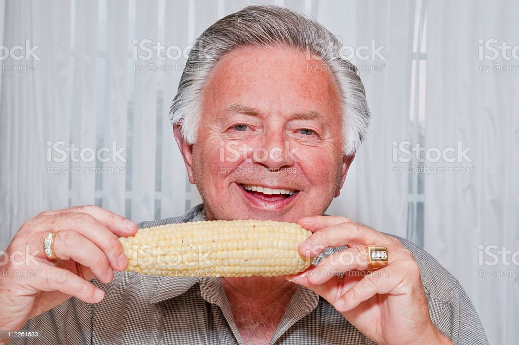 senior man eating corn on the cob stock photo