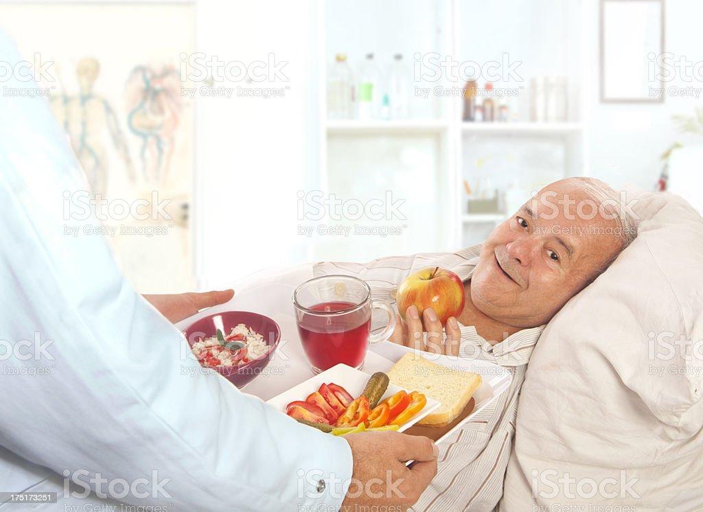 Senior Man Eating Hospital Food In Bed stock photo