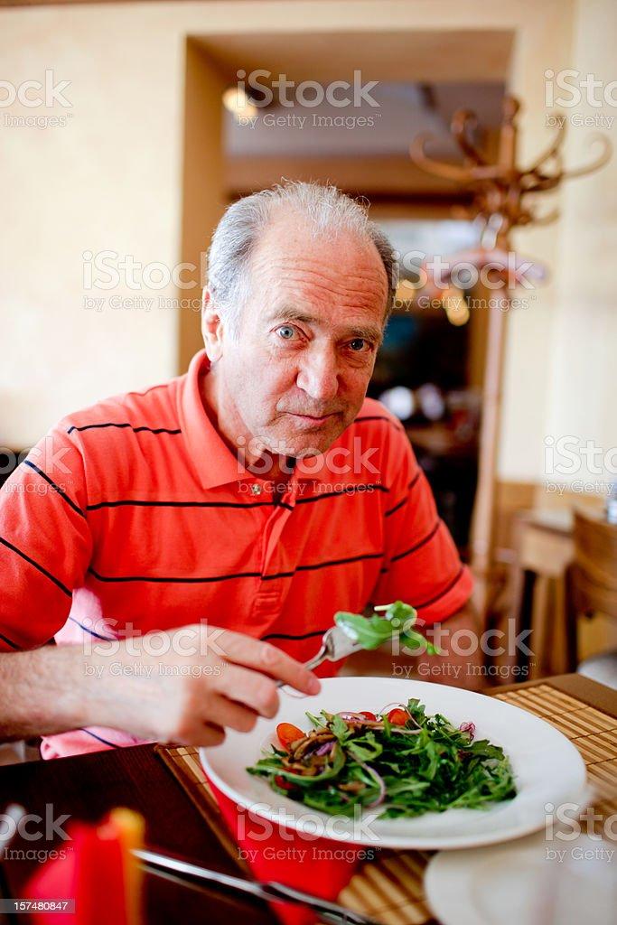 Senior man eating ruccola salad royalty-free stock photo