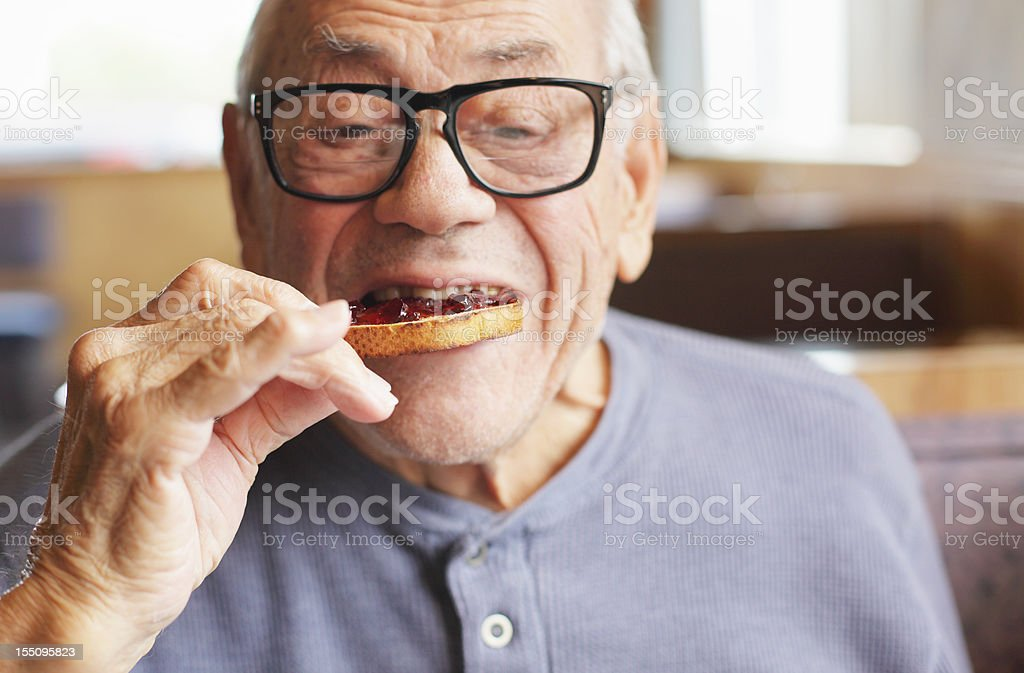 Senior Man Eating Toast and Jelly Jam stock photo