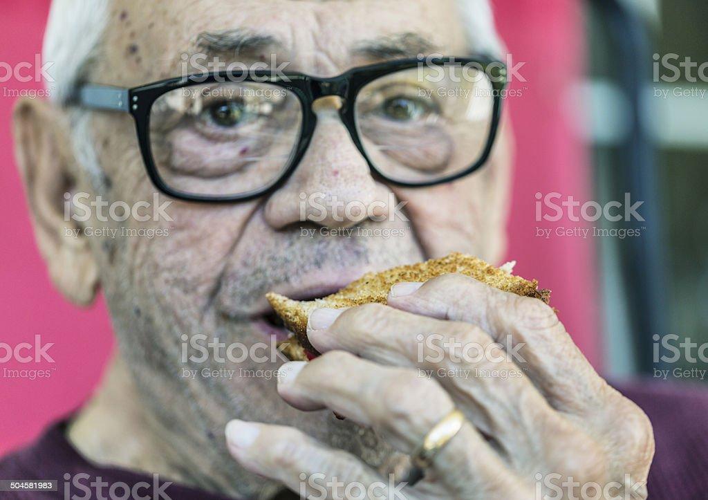 Senior Man Eating Toasted Sandwich stock photo
