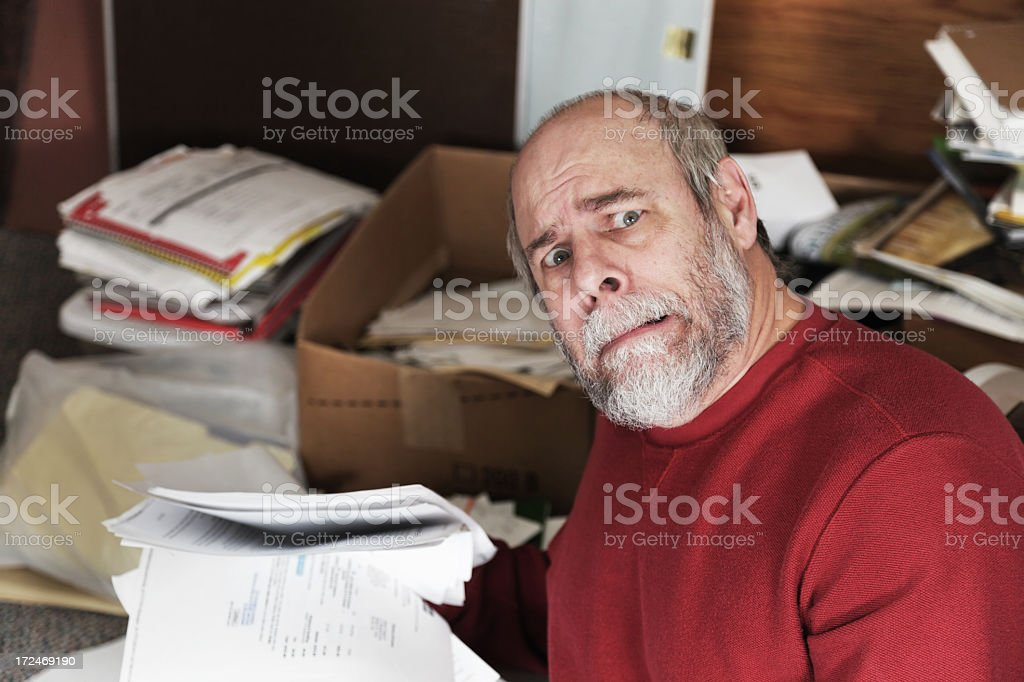 Senior Man Embarrassed By Messy Paperwork stock photo