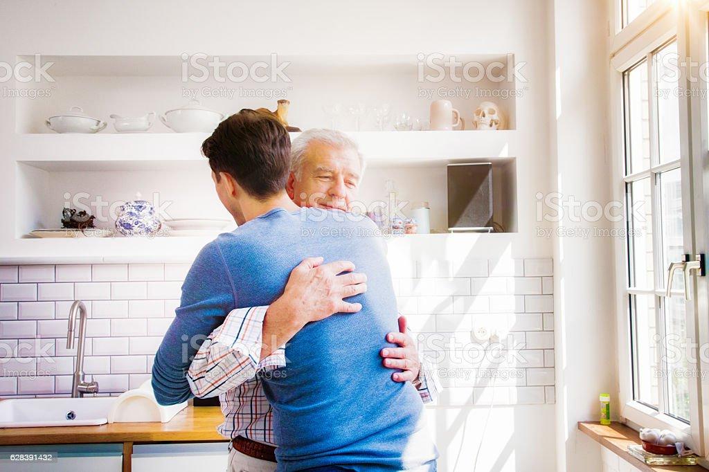 Senior man embraces mature son in sunny kitchen stock photo