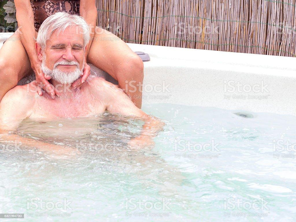 Senior man enjoying neck massage while siting in Jacuzzi pool stock photo
