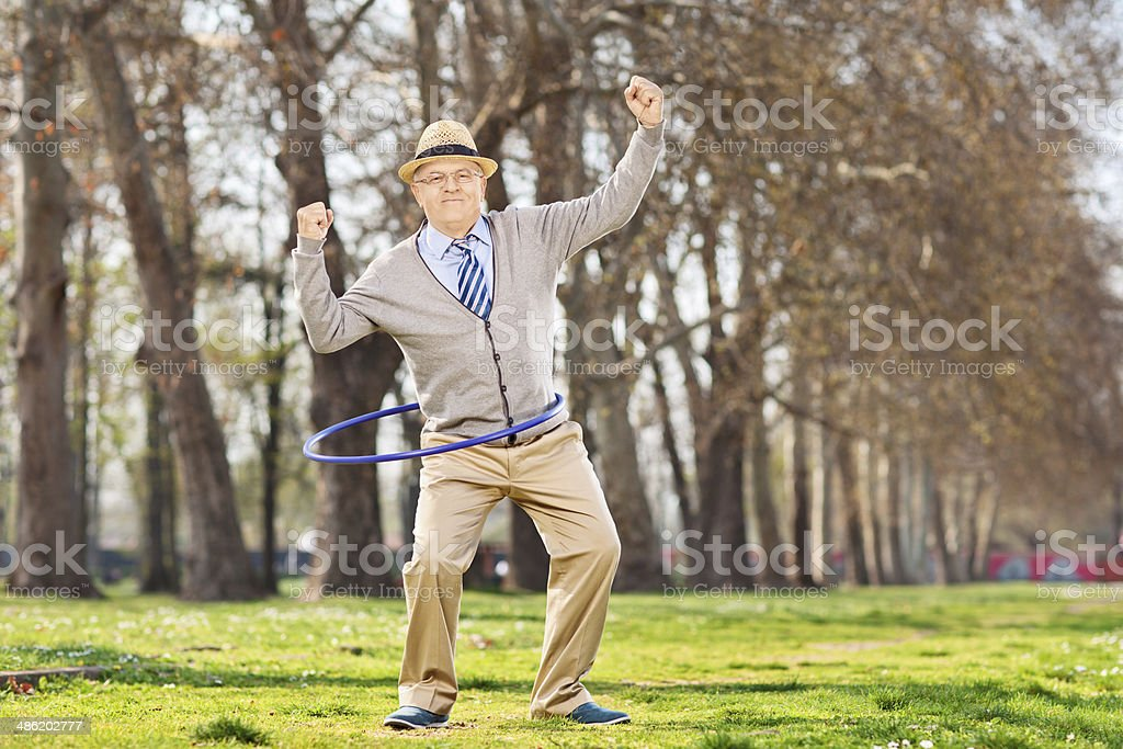 Senior man, exercise with a hula hoop in park stock photo