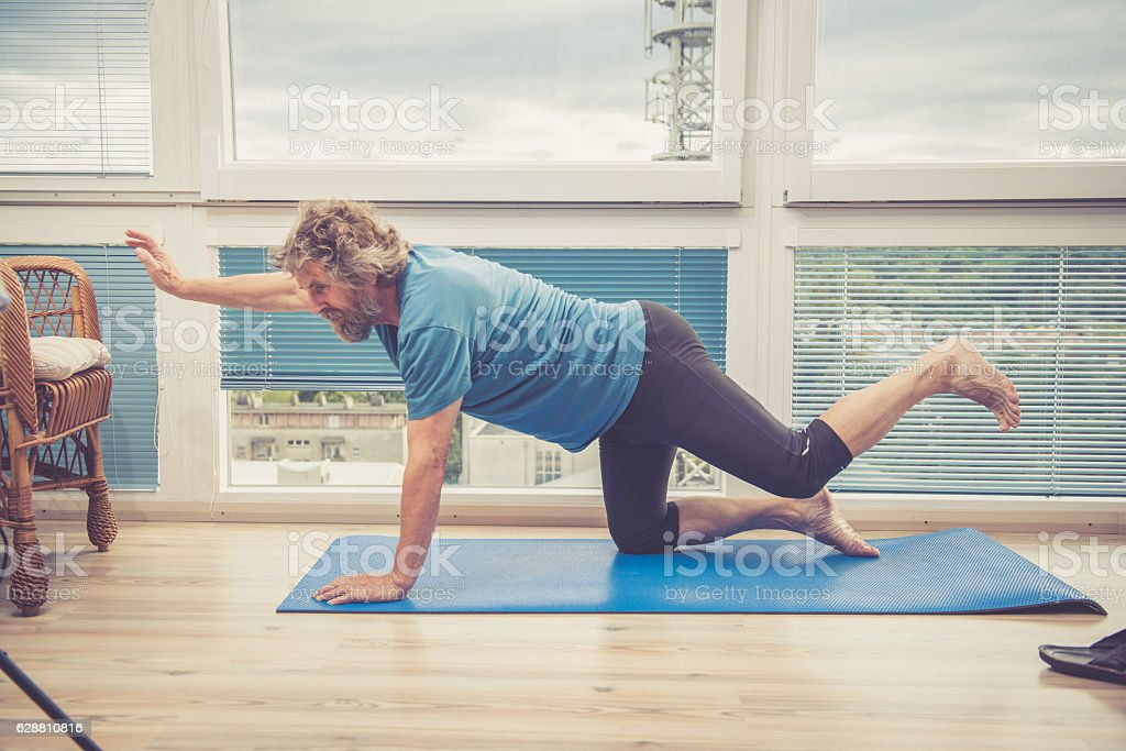 Senior Man exercising at Home - stretching on the floor stock photo