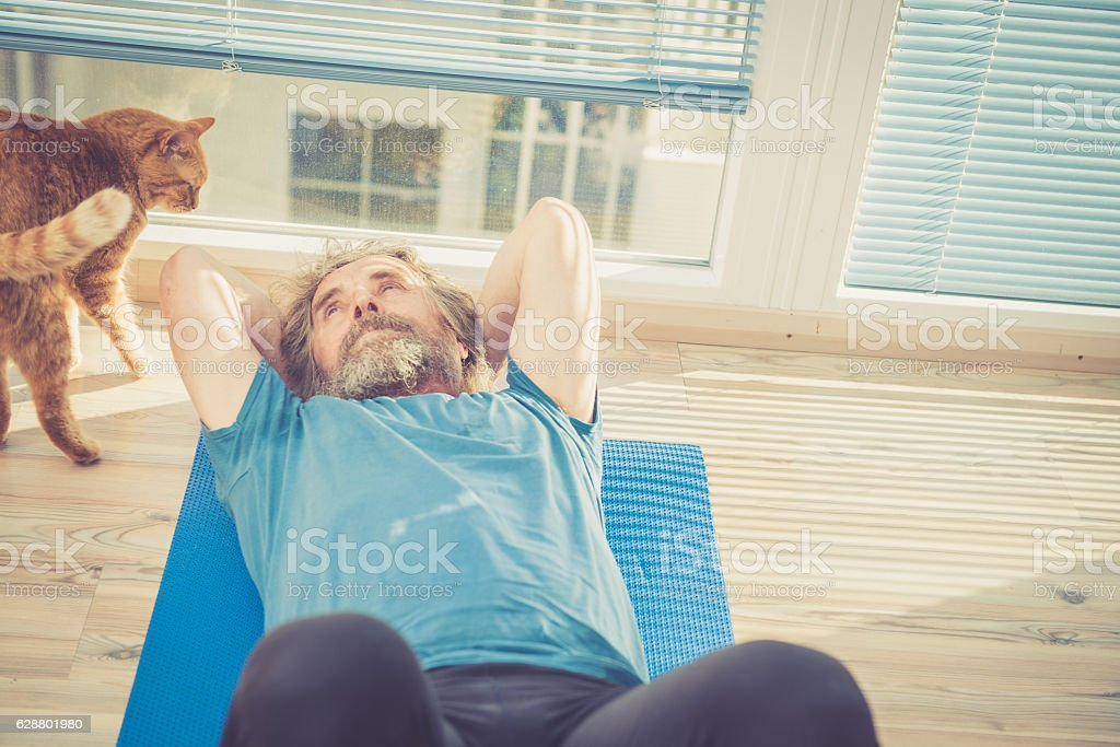Senior Man exercising at Home with his Ginger Cat stock photo