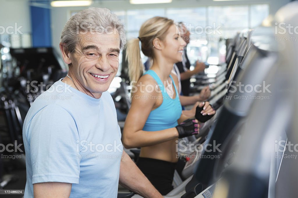Senior man exercising on treadmill in busy fitness club gym royalty-free stock photo