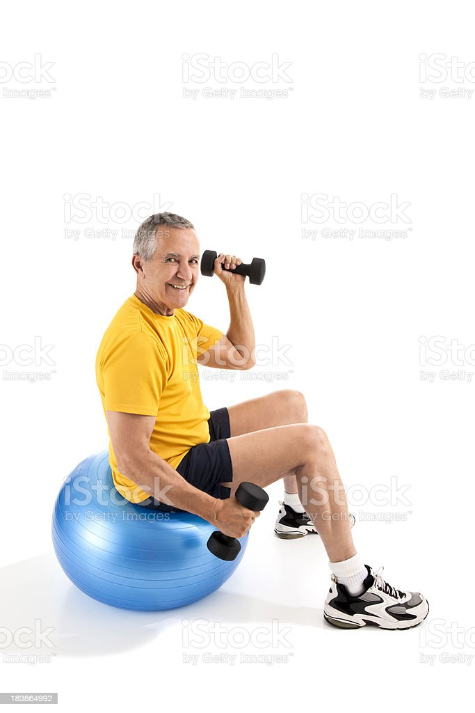 Senior man exercising with dumbells on exercise ball royalty-free stock photo